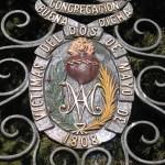 Verja de entrada con el escudo de la sociedad que gestionó el cementerio